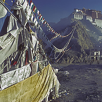 CHINA, TIBET, LHASA. Potala Palace, former abode of Dalai Lama & site of many revered Tibetan Buddhist temples. Prayer flags foreground.