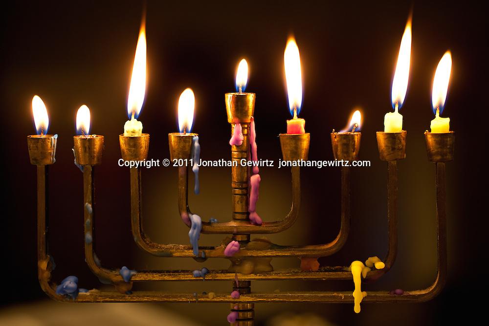 A Hanukka menorah or lamp with burning candles and wax drips.