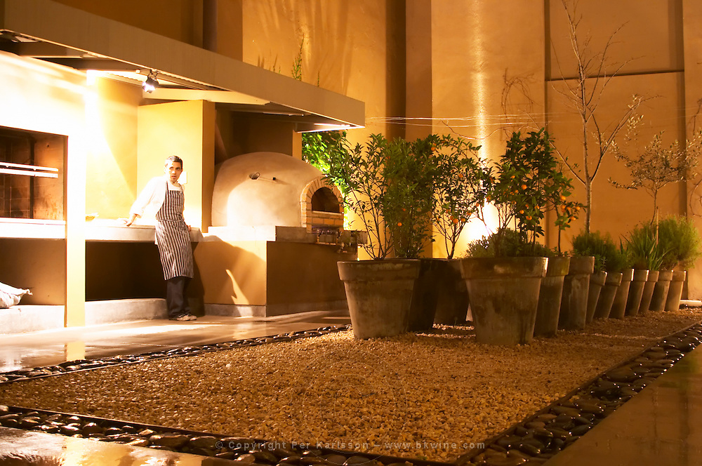 A cook waiting beside the special oven in the garden used to bake bread and other special things. Huge pots of plants, orange trees. The Dolly Irigoyen - famous chef and TV presenter - private restaurant, Buenos Aires Argentina, South America Espacio Dolli