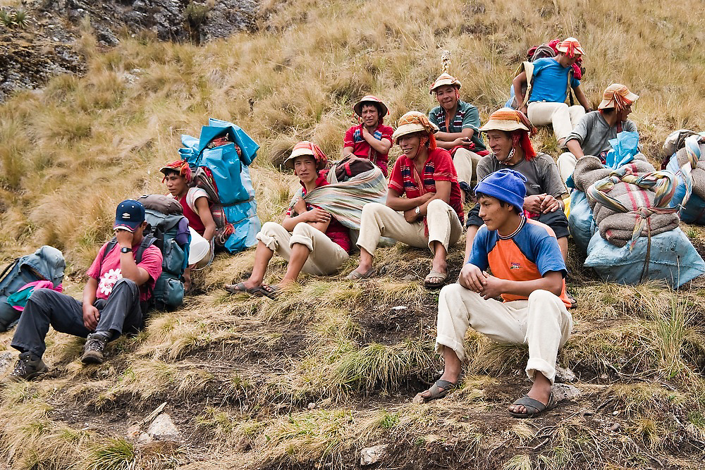A group of porters sit and rest together on a hillside along the Inca Trail to Machu Picchu, Peru.