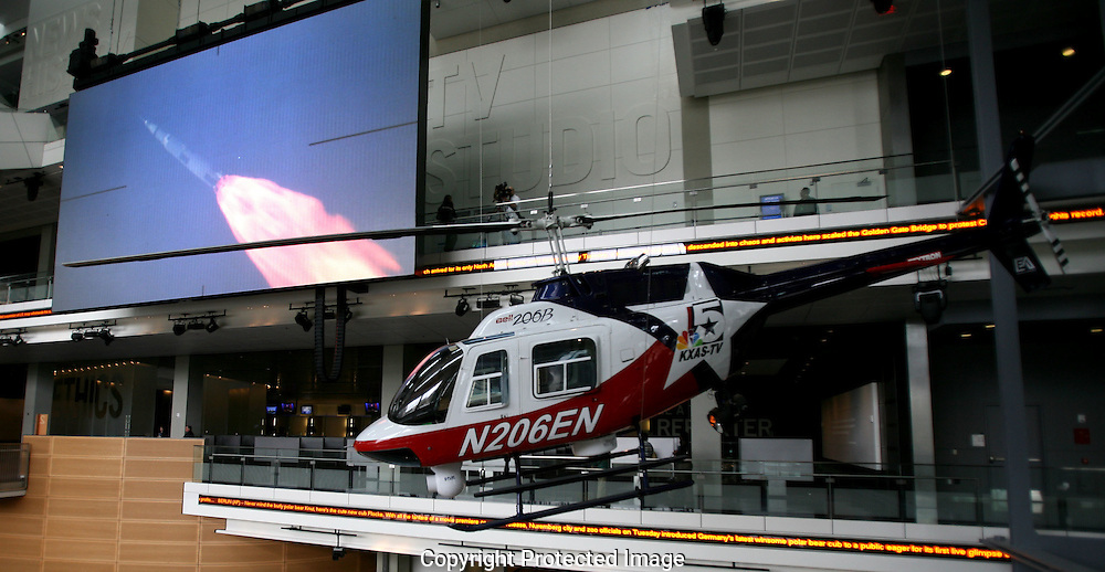 A Bell 206B Jet Ranger helicopter painted to replikcate  one used in the Dallas Fort Worth area and the giant high-definition media screen are on view for visitors in the Great Hall of News  at the Newseum in Washington, DC on April 8, 2008.  Photograph: Dennis Brack