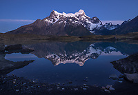 Paine Grande twilight reflects in the calm waters of Lago Nordenerskjold, Torres del Paine National Park, Chile