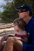 A father and his small daughter on the beach looking out at the surf in Hawaii