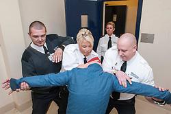 Prisoner being restrained by court staff
