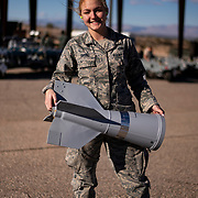 U.S. Air Force Airman 1st Class Nicole Bruno carries a BSU-33 conical fin assembly for a BDU-50 inert bomb at Nellis Air Force Base's 57th Munitions Squadron, March 13, 2019. The Fin stabilizes the inert bomb after it dropped from an aircraft.  (U.S. Air Force photo by Tech. Sgt. Perry Aston)