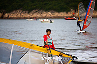 A day of riding the calm seas are over as these teenagers carry their windsurfers out of the water onto the beach at songlanshan.