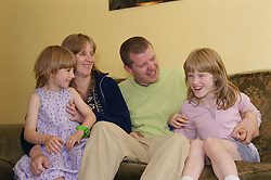 Family sitting together on sofa at home,
