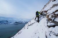 Hiker on winter ascent of Mannen mountain peak, Vestvågøy, Lofoten Islands, Norway