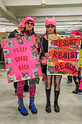 """Two young women wearing pink pussy hats and carry signs throug CIVIC Center BART station en route to the first Women's March San Francisco. One sign reads, """"Pussy grabs back,"""" while the other reads, """"Resist, resist, resist."""""""