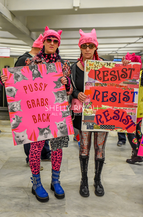 "Two young women wearing pink pussy hats and carry signs throug CIVIC Center BART station en route to the first Women's March San Francisco. One sign reads, ""Pussy grabs back,"" while the other reads, ""Resist, resist, resist."""