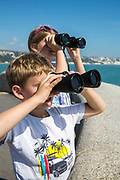 Children on a family holiday use binoculars to search for dolphins from the Kent coast on the 30th of August 2016, Folkestone, Kent, United Kingdom. The boy aged 5 and the girl aged 8 are dressed for the clear blue sky of the summer.