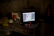 A TV plays static filled image of a Chinese opera program at the home of 77 year old Lu Zhitian and his wife 73 Year old Lu Weishi in a rural village near Fuyang, Anhui Province,  China on 28 August  2013.  As able-bodied adults seek work in cities in hopes of better income, more and more villages in China are inhabited mostly by the elderly and children.