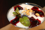 cream dessert garnished with berry sauce and mint leaf
