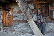 A Kinnauri man takes a break on the steps of an old building in Giabong Village in the Ropa Valley, Himachal Pradesh, India