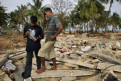 Left, Judeson Britto Moses, who lost his entire immediate family in the tsunami, visits the beach near his wrecked home in the destroyed village of Dutch Bar, Batticaloa, Sri Lanka, Jan. 16, 2005. ÒI am afraid of the beach now,Ó said Moses. Residents of the small Christian village spent more than six weeks in a makeshift refugee camp at the local convent recovering from the devastating tsunami that hit the eastern and southern borders of Sri Lanka. They were then moved into another temporary living camp, while awaiting the building of new homes.