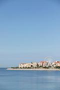 Coastline with city and ferris wheel under clear blue sky, Ajaccio, Corsica, France