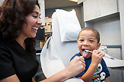 Fun lifestyle image of a boy brushing his teeth in the dentist chair.