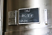 A stainless steel wine fermentation tank with a black chalk board that says BCTF indicating the contents of the vat at Champagne Deutz in Ay, Vallee de la Marne, Champagne, Marne, Ardennes, France, low light grainy grain