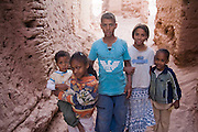 Children pose in a sandy passageway of Ait Bounou, an ancient kasbah, or fortified village, in the Moroccan Sahara. The town is quickly falling into ruin as the inhabitants flee the drying well and the advancement of the dunes expedited by a 16-year drought and the damming of the Draa River.