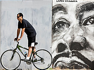 A cyclist rides past a mural painted on a temporary construction wall near the intersection of Niles Avenue and Jefferson Boulevard streets in South Bend on Tuesday. While many have been enjoying the perfect weather the past few days, rainy conditions<br /> are expected to return today. It's an unwelcome forecast as many are still struggling to clean up after last week's historic deluge.