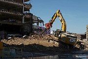 Digger working on tearing down and moving debris and rubble from an old multi storey car park as part of a development / redevelopment of old builindgs in the city centre on 15th June 2021 in Birmingham, United Kingdom. The city is under a long term and major redevelopment, with much of its industrial past being demolished and made into new flats for residential homes, as part of the Big City Plan.