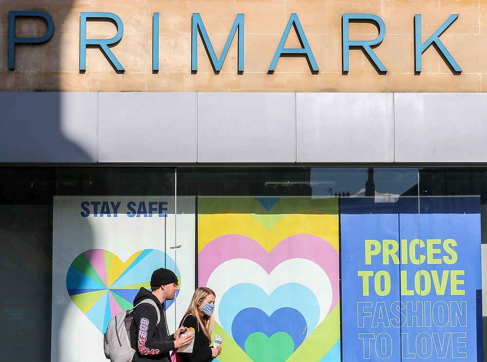 6th March, 2021. Cheltenham, England. A man and woman walk past a shut Primark under the national lockdown restrictions