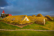 "A farmhouse is said to have stood on the hill at Glaumbær since the Age of the Settlements (900 AD). The present buildings vary in age; the most recent addition having been built in 1876-79, while the oldest – the kitchen, ""long pantry,"" and middle baðstofa – are believed to have been preserved much as they were in the mid-18th century. The passages connecting the individual units have also remained unchanged for many centuries.<br /> <br /> The form of the farmhouse as it is today is similar to that of many large farmhouses in Skagafjördur from the 18th and 19th centuries. Between 1879 and 1939, the farmhouse at Glaumbær remained unchanged; it was repaired and declared a conserved site in 1947, the year the last inhabitants moved out. An English benefactor, Sir Mark Watson, contributed a gift of £ 200 for the renovation of the farmhouse, which was crucial to its preservation. <br /> <br /> The farmhouse is built of turf, stones, and timber. The walls are built of stones and of pieces of turf layed up in a herringbone pattern, with long turf strips between the layers. The Glaumbær estate provided little rock suitable for building purposes, but it has plenty of good turf, so the walls of the farmhouse contain relatively little rock; it was used only at the base of the walls to prevent damp from rising up into them. Imported timber and driftwood were used in the interior frame and paneling. <br /> <br /> The farmhouse consists of a total of 13 buildings (houses), each of which had its own function. The main unit is the baðstofa, a communal eating/sleeping room, where people sat to do their handiwork. Food was stored and prepared in the pantry and kitchen. The front hall, passages, and south entrance (Brandahús) provided access throughout the farmhouse. One house provided accommodation for the elders and other members of the household. There are two guest rooms, two storerooms, and a smithy (blacksmith's workshop). Many of the pastors of Glaumbær were skilled in metalwork."