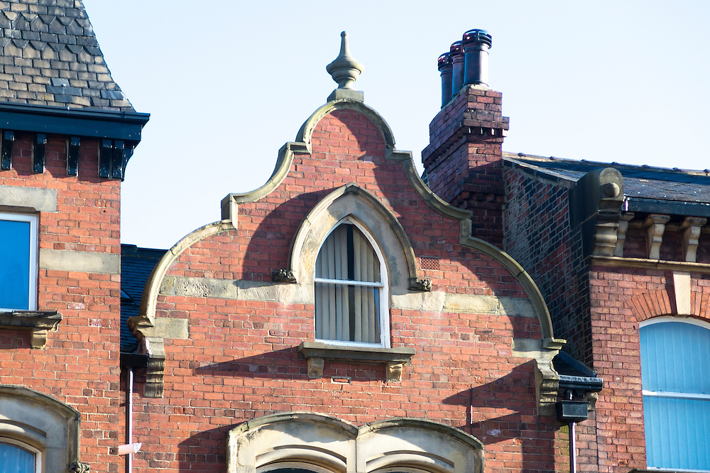 Brick Victorian Dutch Gable on Woodhouse Lane Leeds,  Yorkshire, UK -  with stone finial and Gothic arched window with hood mould