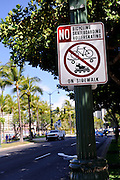 Street sign prohibiting bicycling, skateboarding and rollerskating on sidewalk. Waikiki, Honolulu, Hawaii RIGHTS MANAGED LICENSE AVAILABLE FROM www.PhotoLibrary.com
