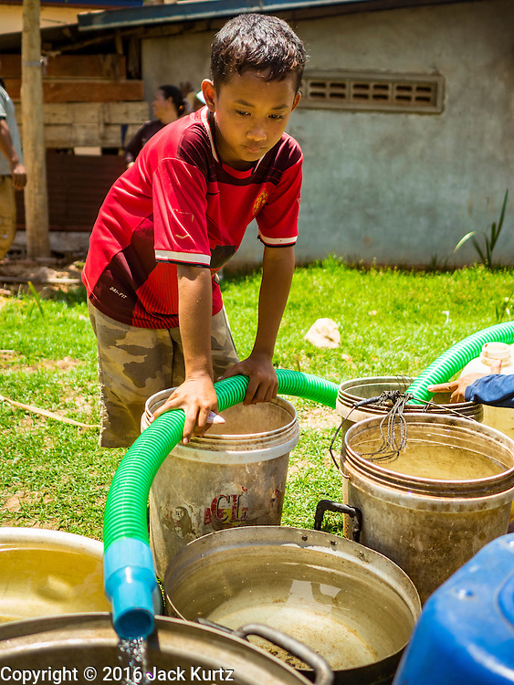 03 JUNE 2016 - SIEM REAP, CAMBODIA: A child helps fill his family's water jugs a water distribution point in Sot Nikum, a village northeast of Siem Reap. Wells in the village have been dry for more than three months because of the drought that is gripping most of Southeast Asia. People in the community rely on water they have to buy from water sellers or water brought in by NGOs. They were waiting for water brought in by truck from Siem Reap by Water on Wheels, a NGO in Siem Reap. Cambodia is in the second year of  a record shattering drought, brought on by climate change and the El Niño weather pattern. There is no water to irrigate the farm fields and many of the wells in the area have run dry.     PHOTO BY JACK KURTZ