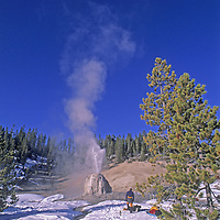 A cross country skier admires Lone Star Geyser in Yellowstone National Park, Wyoming.