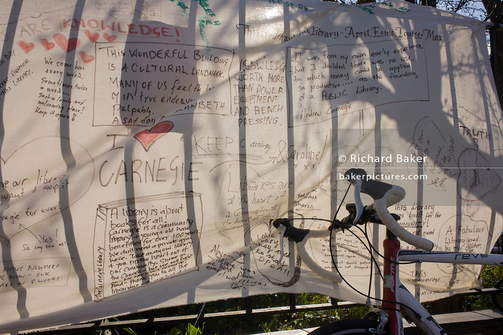 Protesters have shown their feelings with banner messages including one quoting steel magnate Andrew Carnegie outside Carnegie Library in Herne Hill, south London while occupiers remain inside the premises on day 6 of its occupation, 5th April 2016. The angry local community in the south London borough have occupied their important resource for learning and social hub for the weekend. After a long campaign by locals, Lambeth have gone ahead and closed the library's doors for the last time because they say, cuts to their budget mean millions must be saved.