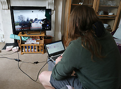 A man watches TV while working on his laptop from home in London. Issue date: Thursday April 2, 2020.