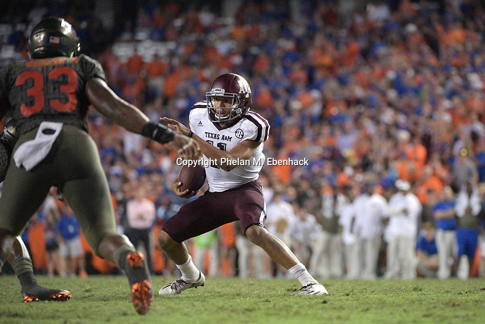 Texas A&M quarterback Kellen Mond (11) rushes for yardage in front of Florida linebacker David Reese (33) during the second half of an NCAA college football game Saturday, Oct. 14, 2017, in Gainesville, Fla. Texas A&M won 19-17. (Photo by Phelan M. Ebenhack)