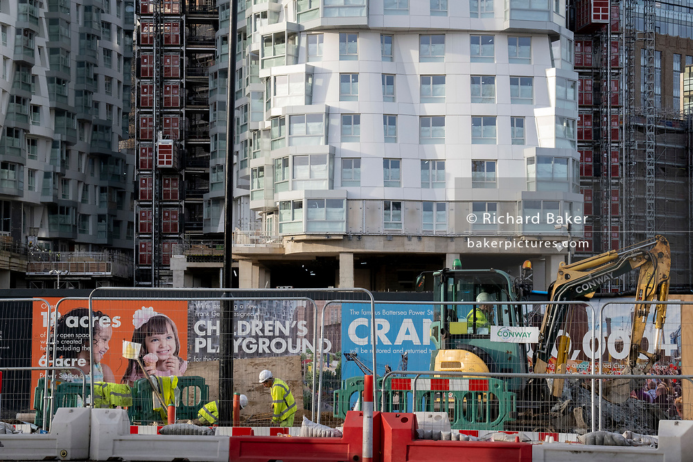 Construction workers carry on the development at Nine Elms, Battersea, during the second lockdown of the UK's Coronavirus pandemic, when all but essential retailers and businesses remain shut according to the government's restriction rules, on 13th November 2020, in London, England.