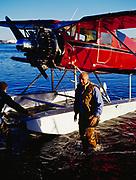 Jimmy Branham by his 1934 Waco biplane on floats, Lake Hood, Anchorage, Alaska.