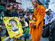 13 OCTOBER - BANGKOK, THAILAND: Buddhist monks walk past a portrait of the late king on the first anniversary of the death of Bhumibol Adulyadej, the Late King of Thailand. About 199 monks from 14 Buddhist temples in Bangkok participated in the mass merit making at Siriraj Hospital to mark the anniversary of the revered King's death. He will be cremated on 26 October 2017.  PHOTO BY JACK KURTZ