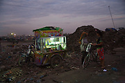 RUBBISH DUMP RECYCLING. South East Asia, Cambodia, Phnom Penh. Smokey Mountain, Steung Mean Chey, is Phnom Penh's municipal rubbish dump. Thousands work there, some 600 minors and 2000 adults, recycling the city's rubbish, dumped there by garbage trucks every day. The dump is notorious as many very young children work there. People eat and sleep overnight in the rubbish and fumes, under plastic tarpaulins or in the open air. They work 24 hours a day, like miners, with headlamps at night, collecting plastic, metals, wood, cloth & paper, which they sort and clean, weigh and sell, to be carried away for recycling. A day's work typically brings less than a dollar per person. One and a half to two dollars per day per family. The overpowering, acrid odour of grey smokey fumes blows across the dump, from which the place gets its name 'Smokey Mountain'. It can be smelt miles away. The shantytowns and squats, the recycling worker's homes butt onto or are inside the dump itself. There is no running water, sanitation and many are ill. Children often work with friends or relatives. Religious and ngo's help some children, but this is often resisted by families who need the extra income they generate.///Fast-food mobile vendor selling snacks and drinks, as night approaches, on the edge of Smokey Mountain