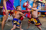 23 DECEMBER 2014 - BANGKOK, THAILAND: Boys spar on the floor in the Kanisorn gym in Bangkok. The Kanisorn boxing gym is a small gym along the Wong Wian Yai - Samut Sakhon train tracks. Young people from the nearby communities come to the gym to learn Thai boxing. Muay Thai (Muai Thai) is a mixed martial art developed in Thailand. Muay Thai became widespread internationally in the twentieth century, when Thai boxers defeated other well known boxers. A professional league is governed by the World Muay Thai Council. Muay Thai is frequently seen as a way out of poverty for young Thais. Muay Thai professionals and champions are often celebrities in Thailand.     PHOTO BY JACK KURTZ