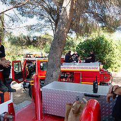 Suivi durant 24 heures de l'activité de pompiers, en majorité volontaires, du SDIS 13, déployés en GIFF (Groupe d'Intervention Feu de Forêt) pour lutter contre les départs d'incendie. En attente sur leur position en bordure d'axe routier, les sapeurs-pompiers occupent leur temps comme ils le peuvent: dans la VLTT le chef de groupe avance son travail de bureau, certains font la sieste allongés sur les cabines des CCF, tandis que d'autres discutent à l'arrière des camions... En ayant toujours une radio allumée à portée d'oreille. Août 2021 / Bouches-du-Rhône (13) / FRANCE<br /> Voir toutes les photos de ce reportage (89 photos) https://sandrachenugodefroy.photoshelter.com/gallery/2021-08-GIFF-du-SDIS13-Complet/G0000lDeWrBxRkHY/C0000yuz5WpdBLSQ