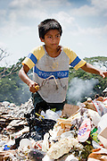 09 NOVEMBER 2004 - TAPACHULA, CHIAPAS, MEXICO: Carlos Lopez Perez, 12, works in the municipal garbage dump in Tapachula, Chiapas, Mexico. About 130 people, the poorest of the poor in Tapachula, work in the dump picking through the garbage hoping to find tidbits they can use or sell to brokers who sit on the edge of the dump and resell the garbage. Most of the dump workers are Guatemalan migrants who crossed the border hoping, at one time, to get to the United States. Now they have settled for an existence on the very edge of Mexican society. PHOTO BY JACK KURTZ