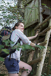 Young female hiker climbing on lookout tower in a forest, Bavaria, Germany