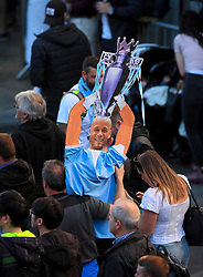 A fan holds a Vincent Kompany cardboard cutout during the trophy parade in Manchester.