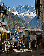 Peaks rise high behind a street and buildings in the village of Lukla, Nepal.