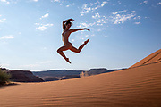 Nude woman leaping in sand dunes in Moab, Utah