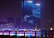 Rizhao City buildings with hi-tech LED moving images of fish, whales and dolphins overlooking the river estuary. Rizhao, Shandong Province, ChinaShandong province, China