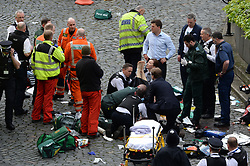 Conservative MP Tobias Ellwood (front, on knee) helps emergency services attend to a police officer outside the Palace of Westminster, London, after a policeman was stabbed and his apparent attacker shot by officers in a major security incident at the Houses of Parliament.