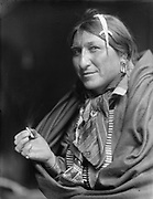 Native North American Indian smoking cigarette.   Photograph by Edward Curtis (1868-1952).