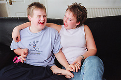 Teenage girl sitting on sofa in living room with arm around brother with Downs Syndrome,