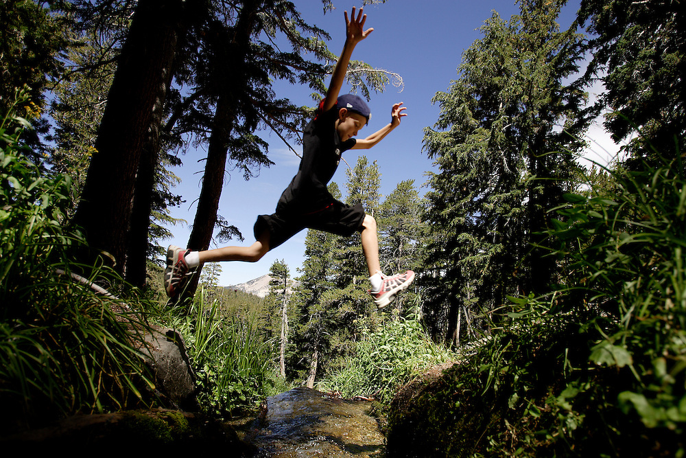 A young boy leaps over Coldwater Canyon Creek that leads into Emerald Lake while hiking in Mammoth, California. Model released.